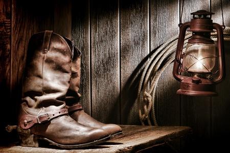 rodeo americano: El viejo Oeste americano del rodeo vaquero tradicionales botas de cuero con Roper aut�nticos estribaciones occidentales de montar en un banco de madera vieja en un granero rancho de �poca iluminada por una l�mpara de queroseno nostalgia