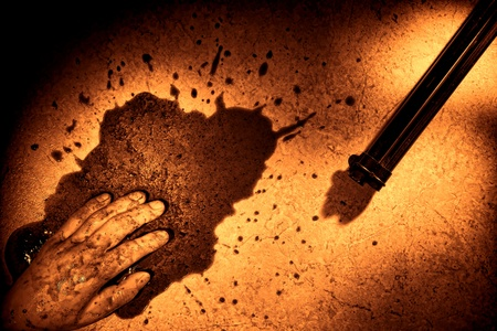 Gruesome forensic crime scene of a violent murder or suicide death (to be determined by Medical Examiner) with dead man hand in a splatter of blood next to a gun weapon on floor during a police criminal investigation in rough grunge sepia