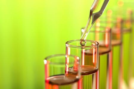 material de vidrio: Laboratorio de pipeta de vidrio con la gota de líquido en tubos de ensayo de un experimento en un laboratorio de investigación en ciencias
