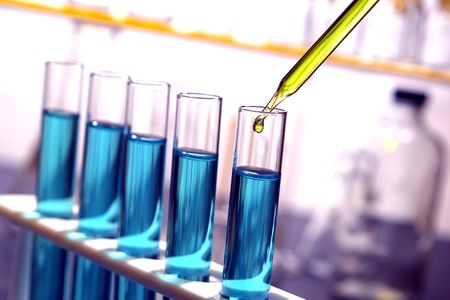 Laboratory pipette with drop of yellow liquid over test tubes filled with blue chemical solution for an experiment in a science research lab