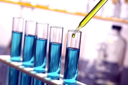Laboratorium pipet met druppel gele vloeistof meer dan reageerbuisjes gevuld met blauwe chemische oplossing voor een experiment in een wetenschappelijk onderzoekslaboratorium