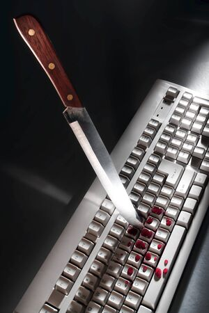 Bloody cyber crime attack scene with a knife as a violent stabbing weapon planted into a computer keyboard with splattered blood as metaphor for online criminal activity and Internet violence danger Фото со стока