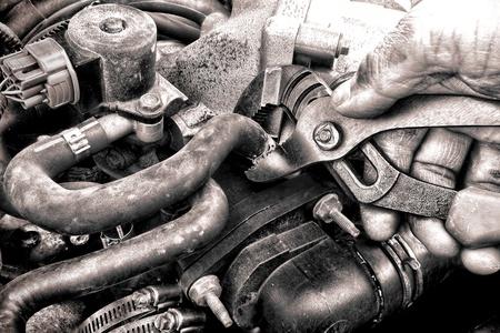 고치다: 자동차 수리 기계공은 기름기가 손에 더러운 그리스가 자동차 상점 유지 보수 설치 서비스를 호출하는 동안 자동차 엔진에 모터 부품 교체를 필요로 손상된 호스를 해결하기 위해 펜치 도구를 들고 덮여 스톡 사진