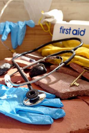 Medische stethoscoop met steriele handschoenen en een verspreide hulpdiensten eerste hulp levert meer dan het bouwen van puin in een natuurramp gebied na een aardbeving of een tornado (geënsceneerde studio afbeelding)