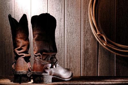 rodeo americano: American West Rodeo Cowboy tradicionales botas de cuero slouch vista el tal�n trasero con cuerda espuelas de montar a caballo del lazo occidental nuevo y aut�ntico lazo colgado en la pared erosionada en un granero de madera vieja Foto de archivo