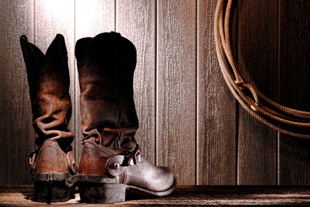 spurs: American West rodeo cowboy traditional leather slouch boots rear heel view with roping riding spurs from back and authentic Western lasso lariat hanging on weathered wall in an old wood barn