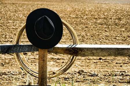 ranching: American West rodeo cowboy black felt hat and roping lasso on a fence post on a ranch
