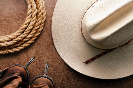 American West rodeo cowboy traditional white straw hat with roping lasso rope and vintage western riding spurs on brown leather boots over hide background  photo