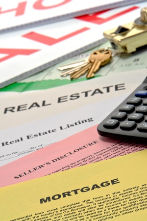 Real estate listing and home seller disclosure broker documents with financial lender mortgage paperwork on busy Realtor desk with keys and sale sign riders in realty agent office Stock Photo