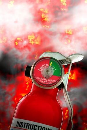 in readiness: Portable dry chemical safety fire extinguisher in front of intense and fiery inferno with burning flames and heavy smoke as metaphor for protection and firefighting readiness