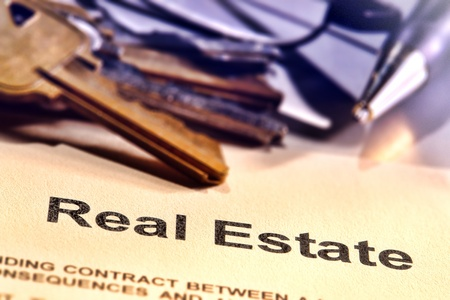 brokerage: Title word real estate on a Realtor broker document contract page with set of house keys and ink pen in a realty brokerage resale office (fictitious document with authentic legal language)