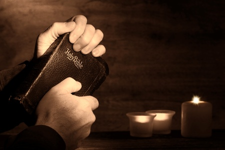 religious service: Praying man hands holding and clinching an old holy bible sacred book in a dark church during a prayer worship service with religious candles glowing in nostalgic aged sepia Stock Photo