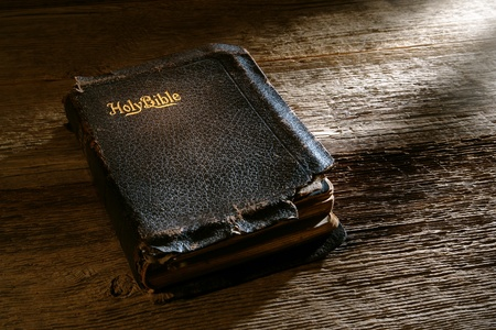 Old antique and damaged holy bible sacred religious book on weathered wood bench in a vintage church Stock Photo