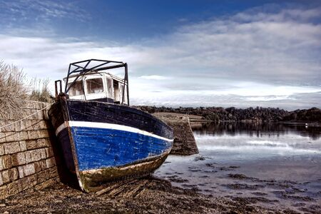 junked: Abandoned old wood fishing boat tied to an old stone masonry dock in an empty estuary river port at low tide in the scenic Brittany region of France  Stock Photo