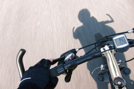 jinete: Ciclista mano con guante de carreras de freno de manillar y tirar de la palanca de punto de vista de piloto en una bicicleta de monta�a por exceso de velocidad por un camino r�pido con efecto de desenfoque de movimiento y velocidad de la sombra ciclista