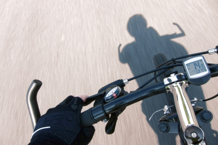 Cyclist hand with racing glove holding handlebar and pulling brake lever rider point of view on a speeding mountain bicycle over a fast road with speed motion blur effect and cyclist shadow   photo