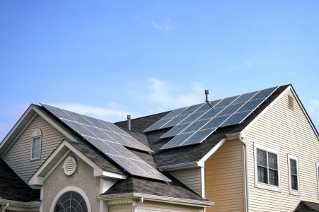 panel: Renewable and clean green energy saving efficient photovoltaic solar panels with different sun expositions on multi gable house roof over blue sky Stock Photo