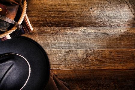 american rodeo: West americano rodeo cowboy cappello di feltro nero con gli strumenti del mestiere e autentici stivali di pelle marroni occidentali con sperone sul vecchio fienile weathered piano ranch in legno come sfondo grunge Archivio Fotografico