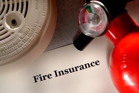 riesgo quimico: Fuego documento de póliza de seguro con detector de humo y extintor de seguridad de emergencia como metáfora de la preparación para desastres y la protección