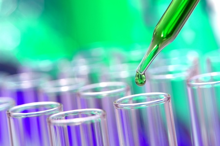 Laboratory pipette with drop of green liquid over test tubes for an experiment in a science research lab photo