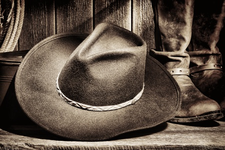 American West rodeo cowboy felt hat and authentic leather western riding boots with vintage ranching gear on weathered wood floor in an old ranch barn Stock Photo - 13265233