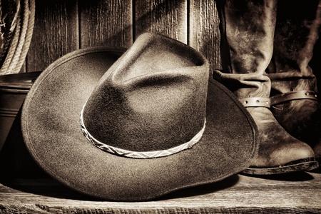 american rodeo: West americano rodeo cowboy cappello di feltro e autentici stivali di pelle monta western con attrezzi d'epoca allevamento sul pavimento di legno stagionato in un fienile vecchio ranch Archivio Fotografico