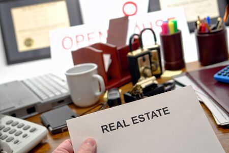 resale: Blank document in agent hand with real estate title page over successful and busy Realtor desk in realty broker sales office with tools of the trade and business supplies