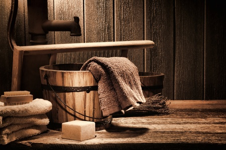 Antique laundry manual washing scene with old towels and ancient natural soap bar near vintage wood bucket and washboard on an aged historic house wooden wash counter Stock Photo
