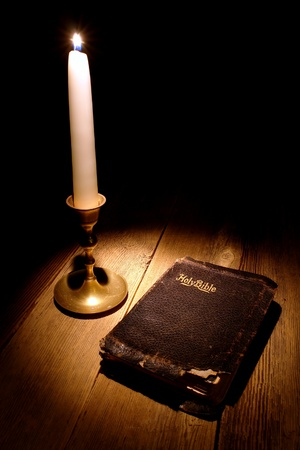 christian candle: Old and damaged Holy Bible antique religious book with torn cover lit by the soft and warm glow of a candle light on a vintage candlestick on an aged wood table  Stock Photo