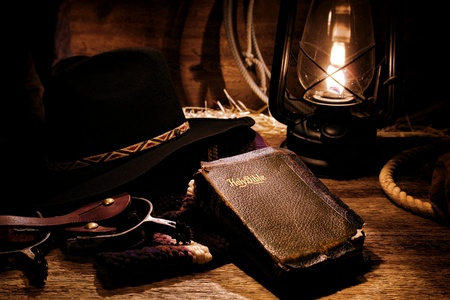 American West rodeo cowboy antique old and worn Holy Bible Christian prayer religious book with traditional ranching gear and authentic western hat lit by vintage kerosene lantern light during night rest at camp