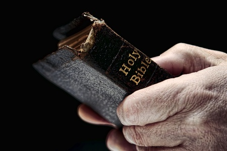 religious service: Aged man hands firmly holding and clinching an old and damaged antique Holy Bible Christian religious book during a religious prayer service in a protestant church Stock Photo