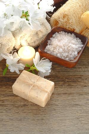 artisanale: Natuurlijke Marseille artisanale aromatherapie gezichts-en lichaamsverzorging bad zeep vastgebonden met organische raffia touw en baden zouten met bloemen en handdoeken op houten tafel in een holistische zorg en rustgevende ontspanning spa Stockfoto