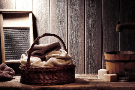 Pile of dry towels in an old wicker basket ready for wash with soap near an antique wood washboard and an aged wooden bucket under a water spigot in a vintage washing laundry