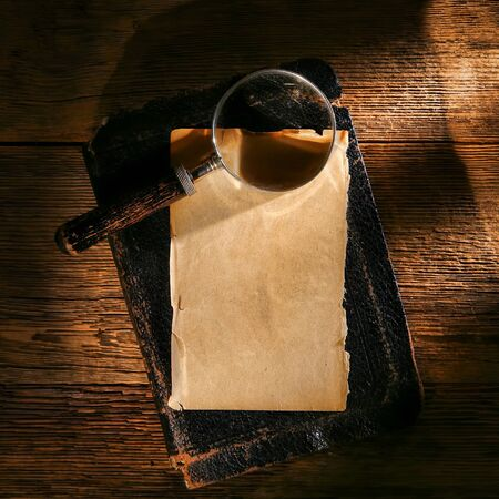 old leather: Old magnifier on a sheet of antique parchment paper on an aged vintage book with used damaged leather cover over weathered wood background