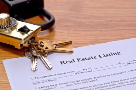 listing: Corredor de bienes ra�ces lista hogar vendedor documento en el escritorio de agente de bienes ra�ces con llaves de la casa y de la seguridad que muestra caja de seguridad en el escritorio de la oficina de bienes ra�ces agente Foto de archivo