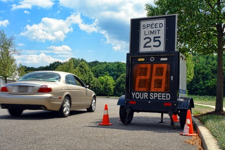 Car driving too fast by a police speed limit monitor trailer in a residential neighborhood Stock Photo