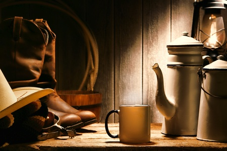 emalj: Amerikanska västern rodeo cowboy autentiska arbetsredskapen med äkta hatt och läderranchägare stövlar på en gammal trä bord med vintage kopp och stål emalj kanna kaffe för en paus i en antik ranch lada Stockfoto