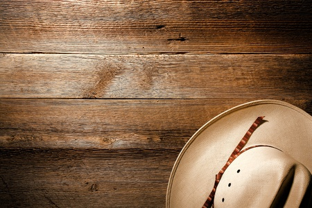 American West authentic white straw cowboy hat on old and aged western saloon floor wood plank background photo