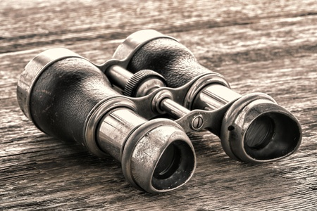 Old and used vintage distance viewing binocular optics pair on antique and weathered aged wood board Stock Photo