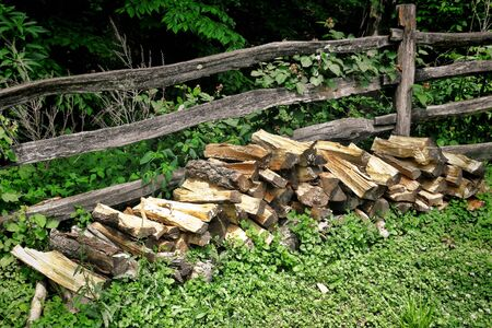 split rail: Pile of split fire wood logs against an old rail and post fence in the woods as fuel reserve for traditional rural heating  Stock Photo