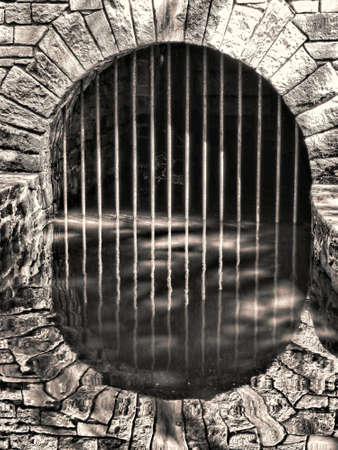 ancient prison: Old and mysterious underground water tunnel with ancient stone arch and metal bars with its reflection on an antique historic building   Stock Photo