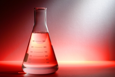 Scientific laboratory glass conical Erlenmeyer flask filled with clear chemical liquid for a chemistry experiment in a science research lab Imagens - 13846374
