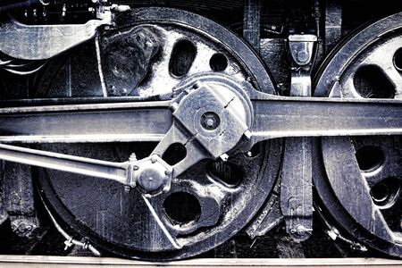Vintage steam locomotive driving wheel and rods gear assembly in old grunge industrial photo