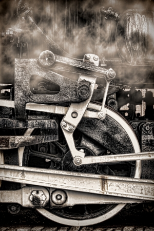 Old steam locomotive vintage running gear with antique driving wheels and rods assembly with steam smoke in nostalgic grunge sepia