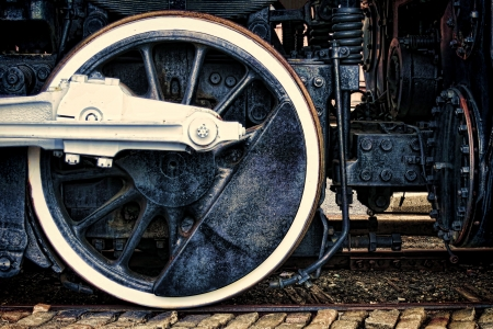 Old steam locomotive vintage running gear with driving wheel and rods assembly in grunge industrial photo