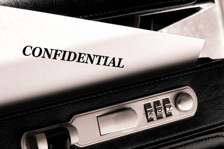 private information: Confidential document letter sticking out of a little ajar open briefcase during a top secret classified information exchange and review meeting Stock Photo