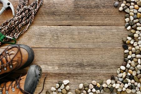 calzado de seguridad: Fondo de la roca de escalada con cuerda de seguridad y los zapatos tradicionales de senderismo de montaña en tablón viejo tablero de madera con piedras de río alpinos