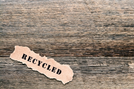 The ecological title word recycled printed on a piece of torn brown paper on reclaimed barnwood lumber wooden background as metaphor for the responsible environmental recycling and reuse of old natural material Stock Photo - 14037736