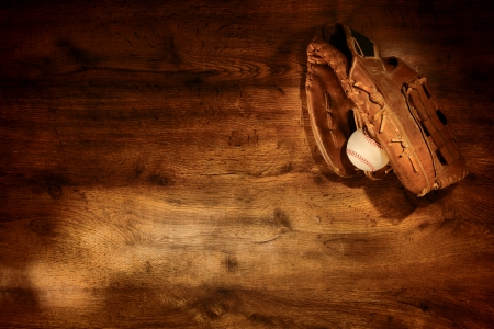 Old worn leather baseball glove and used ball on nostalgic Americana sport wood plank background