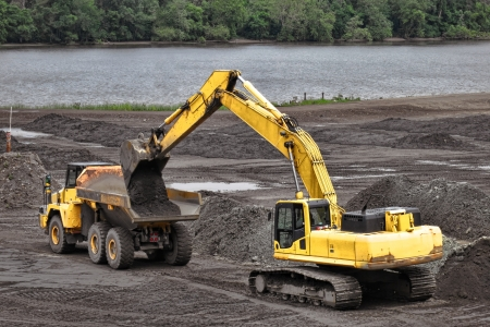 Hydraulic excavator loading dirt load from its scoop into an articulated dump truck on a construction work site photo
